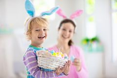Mother and kids, family coloring Easter eggs. Mother and kids color Easter eggs. Little boy with bunny ears showing mom colorful candy eggs after Easter egg hunt stock images