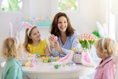Mother and kids, family coloring Easter eggs. Mother and kids color Easter eggs. Mom, little girl and boy with bunny ears dying and painting for Easter egg hunt royalty free stock photo