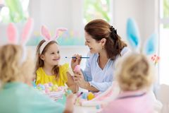 Mother and kids, family coloring Easter eggs. Mother and kids color Easter eggs. Mom, little girl and boy with bunny ears dying and painting for Easter egg hunt royalty free stock image