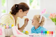 Mother and kids, family coloring Easter eggs. Mother and kids color Easter eggs. Face painting for little child. Little boy with bunny ears and mom dye eggs royalty free stock photos