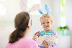 Mother and kids, family coloring Easter eggs. Mother and kids color Easter eggs. Little boy with bunny ears showing mom colorful candy eggs after Easter egg hunt stock photography