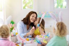 Mother and kids, family coloring Easter eggs. Mother and kids color Easter eggs. Mom, little girl and boy with bunny ears dying and painting for Easter egg hunt stock images