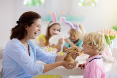 Mother and kids, family coloring Easter eggs. Mother and kids with pet rabbit color Easter eggs. Mom, little girl and boy with bunny ears dying and painting for royalty free stock image