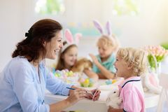 Mother and kids, family coloring Easter eggs. Mother and kids with pet rabbit color Easter eggs. Mom, little girl and boy with bunny ears dying and painting for stock photography