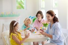 Mother and kids, family coloring Easter eggs. Mother and kids with pet rabbit color Easter eggs. Mom, little girl and boy with bunny ears dying and painting for royalty free stock images