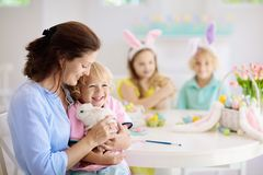 Mother and kids, family coloring Easter eggs royalty free stock photography