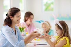 Mother and kids, family coloring Easter eggs. Mother and kids with pet rabbit color Easter eggs. Mom, little girl and boy with bunny ears dying and painting for royalty free stock photography