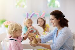 Mother and kids, family coloring Easter eggs. Mother and kids with pet rabbit color Easter eggs. Mom, little girl and boy with bunny ears dying and painting for stock images