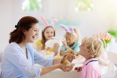 Mother and kids, family coloring Easter eggs stock image