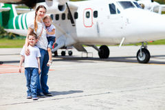 Mother and kids in front of airplane stock photo