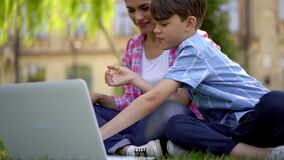 Mother with kids have lesson outdoors using laptop