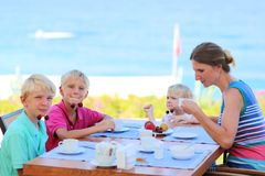 Mother with kids having breakfast in resort restaurant. Happy family of four, mother with three kids, enjoying summer vacation eating healthy breakfast in the royalty free stock images