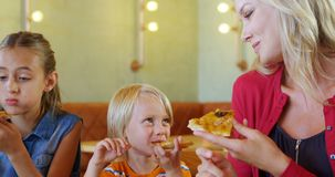 Mother and kids having pizza in restaurant 4k. Happy mother and kids having pizza in restaurant 4k stock video footage