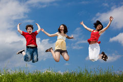 Mother with kids jumping. Active family - mother with kids jumping, running on green meadow stock images