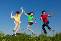 Mother with kids jumping. Active family - mother with kids jumping, running on green meadow royalty free stock photo
