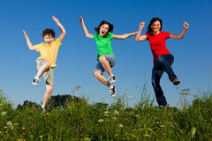 Mother with kids jumping. Active family - mother with kids jumping, running on green meadow Royalty Free Stock Images