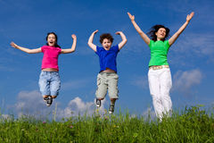 Mother with kids jumping. Active family - mother with kids jumping, running on green meadow Royalty Free Stock Image