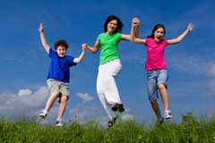 Mother with kids jumping. Active family - mother with kids jumping, running on green meadow Stock Photos