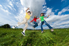 Mother with kids jumping outdoor. Active family - mother with kids running, jumping on green meadow Royalty Free Stock Image