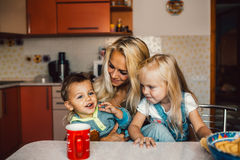 Mother with kids on kitchen Royalty Free Stock Image