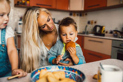 Mother with kids on kitchen Stock Photos