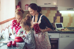 Mother with kids at the kitchen. Mother with her 5 years old kids cooking holiday pie in the kitchen, casual lifestyle photo series in real life interior