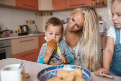 Mother with kids on kitchen, son eats a cookie. Mother with family haveing fun in kitchen, son eats a cookie royalty free stock photos