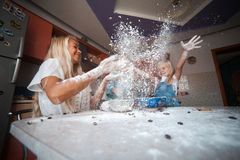 Mother with kids on kitchen throw flour to the top Royalty Free Stock Photo