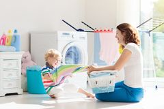 Family in laundry room with washing machine royalty free stock photography
