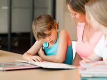 Mother with kids in library Royalty Free Stock Image