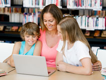 Mother with kids in library Stock Images