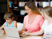 Mother with kids in library Royalty Free Stock Images