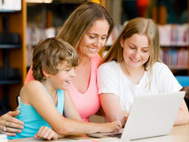 Mother with kids in library Stock Photo