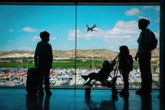 Mother with kids and luggage looking at planes in airport. Family travel stock photography
