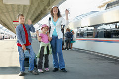 Mother with kids and luggage stands on platform Royalty Free Stock Images