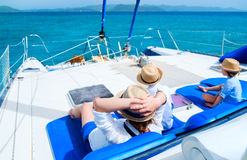 Mother and kids at luxury yacht. Back view of mother and her kids relaxing having great time sailing at luxury yacht or catamaran boat Royalty Free Stock Image
