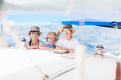 Mother and kids at luxury yacht. Mother and her kids having great time sailing at luxury yacht or catamaran boat Royalty Free Stock Image