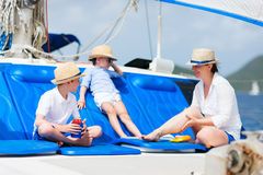 Mother and kids at luxury yacht. Mother and her kids relaxing having great time sailing at luxury yacht or catamaran boat Royalty Free Stock Images