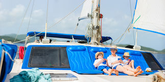 Mother and kids at luxury yacht. Mother and her kids relaxing having great time sailing at luxury yacht or catamaran boat Stock Image