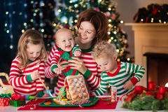 Mother and kids making ginger bread house on Christmas Stock Image