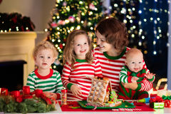 Mother and kids making ginger bread house on Christmas Stock Photo