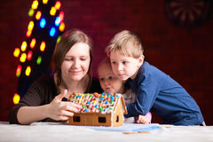 Mother with kids making gingerbread house Stock Image