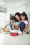 Mother and kids mixing the dough while preparing cookies. In kitchen stock photo