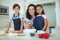 Mother and kids mixing the dough while preparing cookies. Portrait of mother and kids mixing the dough while preparing cookies in kitchen stock photo
