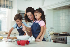Mother and kids mixing the dough while preparing cookies. Portrait of mother and kids mixing the dough while preparing cookies in kitchen royalty free stock photography