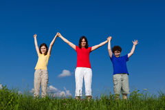 Mother with kids outdoor. Active family - mother with kids jumping, running on green meadow stock photos