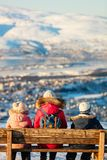Mother and kids outdoors on winter. Back view of beautiful family of mother and kids have a pleasant time on snowy winter day outdoors enjoying views over Tromso Royalty Free Stock Photos