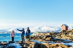 Mother and kids outdoors on winter. Beautiful family of father and kids enjoying snowy winter day outdoors at beach surrounded by fjords in Northern Norway Royalty Free Stock Photos