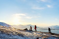 Mother and kids outdoors on winter. Beautiful family of mother and kids have a pleasant time on snowy winter day outdoors enjoying views near Tromso Norway Royalty Free Stock Images