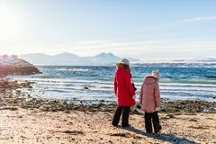 Mother and kids outdoors on winter. Beautiful family of mother and kids enjoying snowy winter day outdoors at beach surrounded by fjords in Northern Norway Stock Photography
